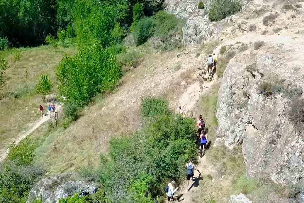 Fotografia de gente haciendo senderismo desde la cascada hasta los ojos de Cabriel